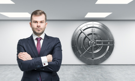 Foto de businessman with arms crossed standing in front of a big locked round metal safe in a bank depository,  a concept of security,  front view, - Imagen libre de derechos