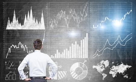 Foto de Research concept with businessman looking at forex charts on dark grey concrete wall - Imagen libre de derechos