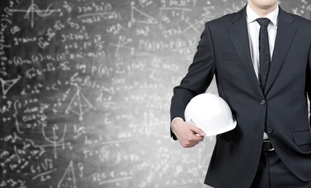 Foto de Businessman with white helmet in hands and business sketch in the background - Imagen libre de derechos