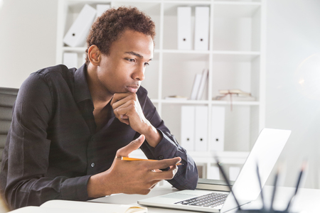 Foto de Pensive black businessman working on project on office desk with laptop and notepad. Bookshelf with documents in the background - Imagen libre de derechos