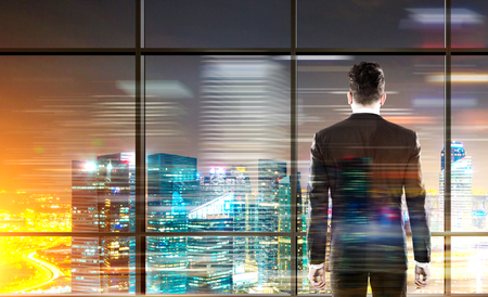 Back view of businessman in suit standing in front of panoramic window and looking at illuminated New York city at night. Double exposure