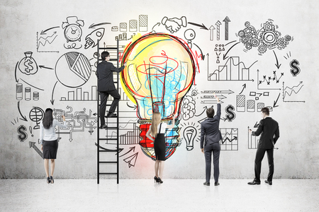 Foto de Rear view of business team standing near concrete wall with colorful light bulb and startup sketch. One man on ladder. Concept of project development - Imagen libre de derechos