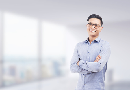 Photo for Smiling Asian businessman in glasses standing with arms folded against blurred office background. Concept of successful startup founder. Mock up - Royalty Free Image