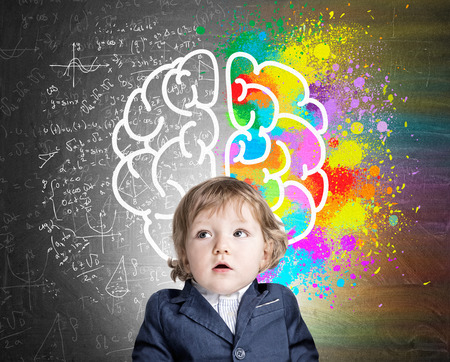 Foto de Portrait of an adorable little boy wearing a suit and standing near a chalkboard with a colorful brain sketch. Concept of child's development - Imagen libre de derechos