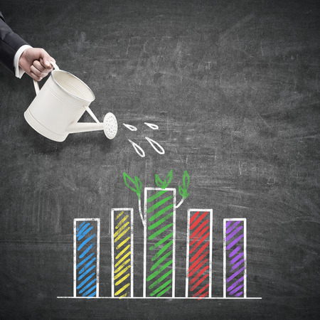 Hand watering colorful business chart on chalkboard background. Financial growth concept