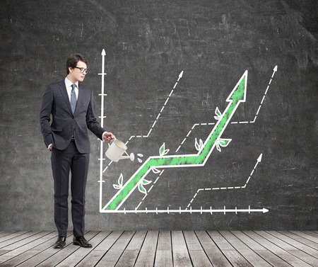Businessman watering creative business graph in room with chalkboard wall and wooden floor. Financial growth concept