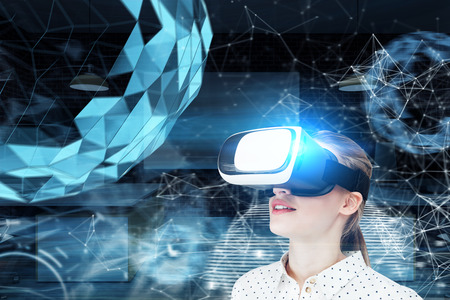 Photo pour Blond girl in a white dotted blouse wearing VR glasses and standing against a blue background with a polygonal orb hologram Toned image double exposure - image libre de droit