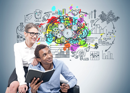 Foto de Smiling African American businessman and his blonde colleague in glasses sitting in an armchair near a gray wall with a colorful brain sketch and gears on it - Imagen libre de derechos