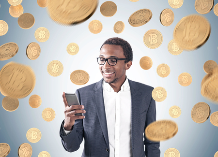 Photo pour Portrait of a young smiling African American businessman wearing a suit and a shirt and looking at his smartphone screen. Gray background, a bitcoin rain - image libre de droit
