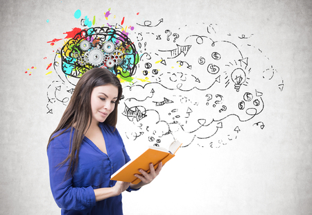 Foto de Portrait of a young smiling businesswoman wearing a blue blouse and reading an orange book. Gray background with arrows and questions marks and a brain with gears above her - Imagen libre de derechos