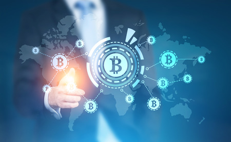 Foto de Businessman with a glowing finger pointing at a bitcoin HUD hologram in the air. Elements of this image furnished by NASA. Toned image double exposure - Imagen libre de derechos