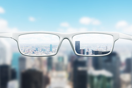 Foto de Day cityscape with skyscrapers and a blue sky as seen through a pair of glasses. Blurred image. - Imagen libre de derechos