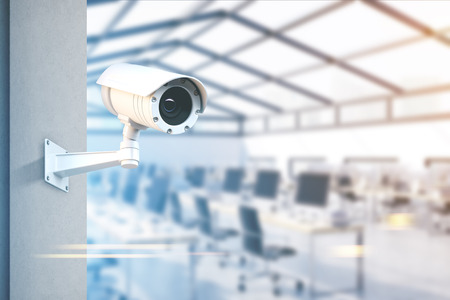 Photo for Modern CCTV camera on a wall. A blurred open space office with rows of computers background. Concept of surveillance and monitoring. Toned image double exposure mock up - Royalty Free Image