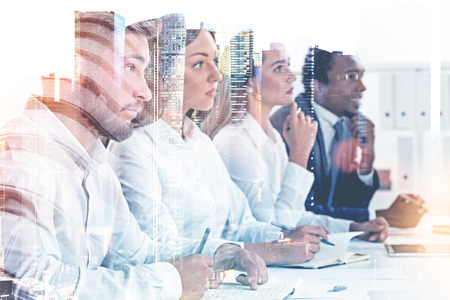 Photo pour Members of a diverse business team sitting together at a table looking forward. A cityscape background. Concept of HR success and job interview. Toned image double exposure mock up. - image libre de droit