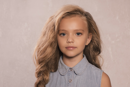 Foto de portrait of cute little 8-9 year old girl with blonde hair, wearing jeans jacket, standing against gray background - Imagen libre de derechos