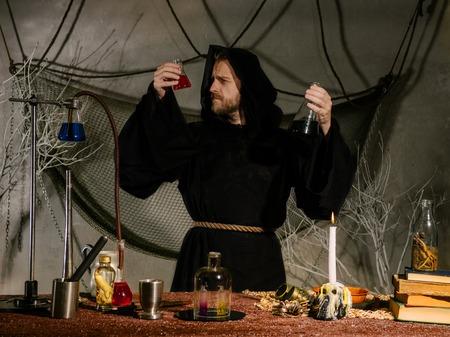 Foto de Portrait of a medieval scientist working in his laboratory. Alchemist. Halloween concept. - Imagen libre de derechos