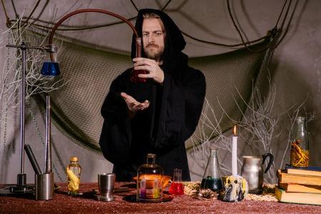 Foto de The medieval alchemist scientist conducts a ritual in his laboratory.. Halloween concept. The bearded magician in the mantle - Imagen libre de derechos