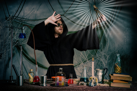 Foto de The medieval alchemist did the philosopher's stone. Covers his face from the light. Scientist inventor steampunk works in his laboratory. Science fiction concept. Halloween. - Imagen libre de derechos