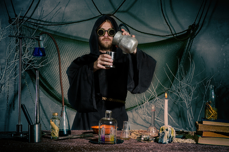 Foto de The alchemist creates an elixir of eternal youth. Scientist inventor steampunk works in his laboratory. Science fiction concept. Halloween. - Imagen libre de derechos