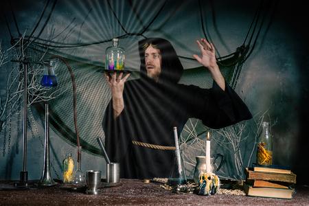 Foto de Portrait of a crazy alchemist's flask. The sorcerer conducts a ritual to receive the elixir of eternal youth. Halloween - Imagen libre de derechos