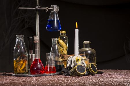 Foto de Halloween.Medieval alchemist's table. Flasks with multi-colored liquids. Scientist-encyclopedist room interior. Old reconstruction - Imagen libre de derechos