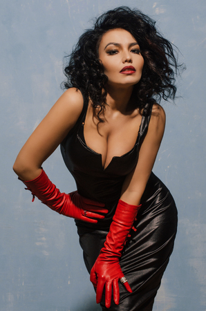 Foto de Beautiful fetish model wearing black spandex dress and long red leather gloves. - Imagen libre de derechos