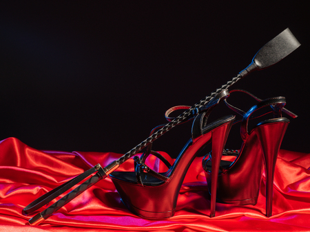Photo pour Adult sex games. Kinky lifestyle. Spank and a pair of black high-heeled shoes on the red linen. Bdsm outfit - Image - image libre de droit