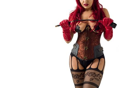 Photo pour Dominant woman in a red wig corset and leather gloves posing on a white background. Mistress holds a whip in her hands a flip flop for punishment - image libre de droit