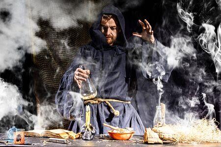 Foto de The medieval alchemist make magic ritual at the table in his smoke laboratory. Halloween concepy background. - Imagen libre de derechos