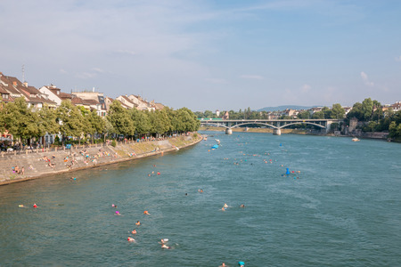 Photo for Basel, Switzerland - June 23, 2017: View on Basel city and river Rhine, Switzerland, Europe. People swim in water. Summer landscape, sunshine weather, blue sky and sunny day - Royalty Free Image