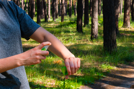 Photo for girl in the forest uses the spray against mosquitoes - Royalty Free Image
