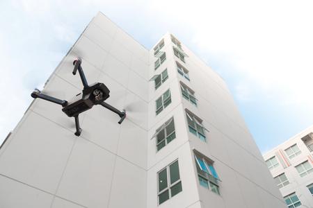 Foto de Drone with high resolution digital camera flying over on residential building background. - Imagen libre de derechos