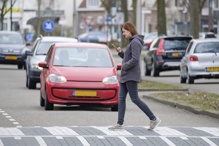 Photo pour young woman walks on the crosswalk and checks her smartphone for messages and does not pay any attention to traffic. - image libre de droit