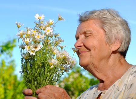Senior smelling flowers on blur sky