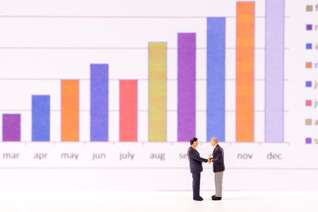 Miniature figure business people looking at bar graph chart