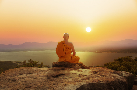 Photo pour Buddhist monk in meditation at beautiful sunset or sunrise background on high mountain - image libre de droit