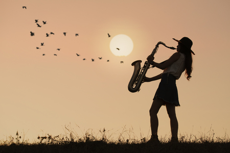 Photo pour Woman play saxophone with sunset or sunrise background - image libre de droit
