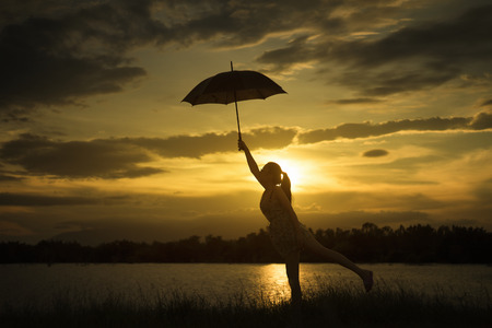 woman holding Umbrella at sunset moment near lake.cloudy sky and big mountain in background.silhouette.jump with umbrella at sunset