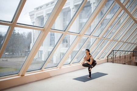 Photo pour Middle aged woman standing in One legged chair exercise, working out, wearing sportswear, full length in front of large window - image libre de droit