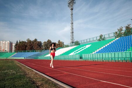 Photo for Full body of girl running track on stadium. Real front view of young woman in pink shorts and tank top and pink sneakers. Outdoors, sport. - Royalty Free Image