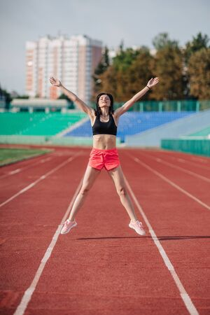 Photo pour Attractive sporty brunette woman in pink shorts and top doing workout with jump rope in sun rays at the stadium. - image libre de droit