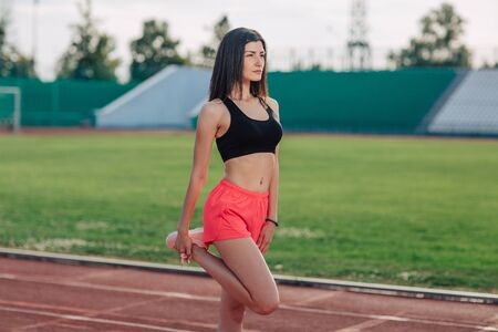 Foto per Young brunette woman athlete in pink shorts and top on stadium sporty lifestyle standing stretching leg side view. - Immagine Royalty Free