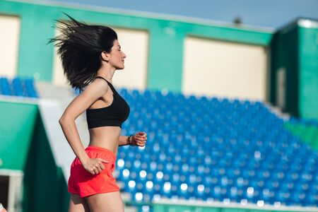 Photo for Girl running track on stadium. Real side view of young woman in pink shorts and tank top and pink sneakers. Outdoors, sport. - Royalty Free Image