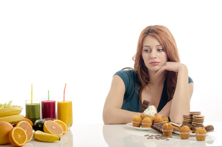 Photo for Woman choosing between fruits, smoothie and organic healthy food against sweets, sugar, lots of candies, unhealthy food. Treating your sweets addiction with fruits and vegetables - Royalty Free Image