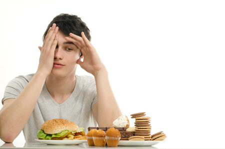 Photo for Young man holding in front lots of cookies and a big hamburger. Choosing between chocolate, cupcakes, biscuits and a burger. Trying to get fat eating fast food and lots of sugar - Royalty Free Image