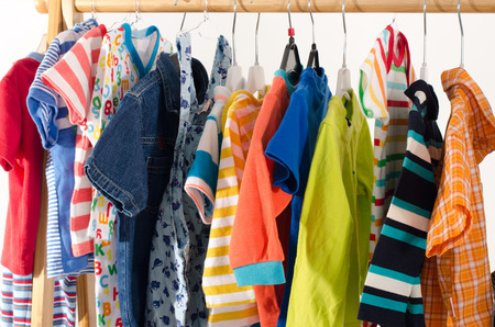 Foto de Dressing closet with clothes arranged on hangers.Colorful wardrobe of newborn,kids, toddlers, babies full of all clothes.Many t-shirts,pants, shirts,blouses, onesie hanging - Imagen libre de derechos