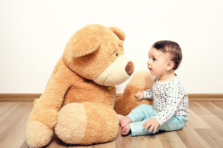 Photo pour Beautiful innocent newborn speaking with his best friend, teddy bear. Adorable baby playing, having fun with his bear toy. Little sweet kid talking and listening his toy - image libre de droit
