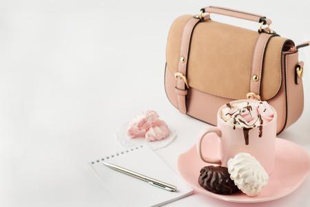 Foto de Hot chocolate with marshmallows, notepad and women's handbag on a white background. Selective focus. - Imagen libre de derechos