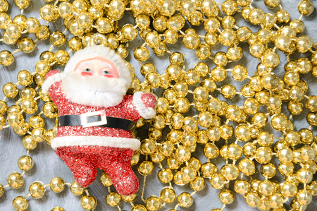 Photo for Christmas toy Santa Claus on golden beads. Close-up. - Royalty Free Image