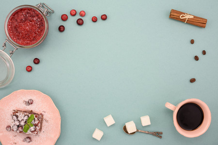Foto de Coffee and chocolate cake with cranberry jam and cinnamon on wooden board, over turquoise background. Top view, copy space. - Imagen libre de derechos